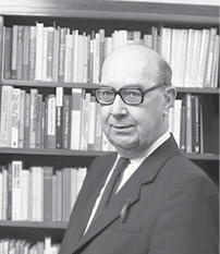 Philip Larkin standing next to a book case